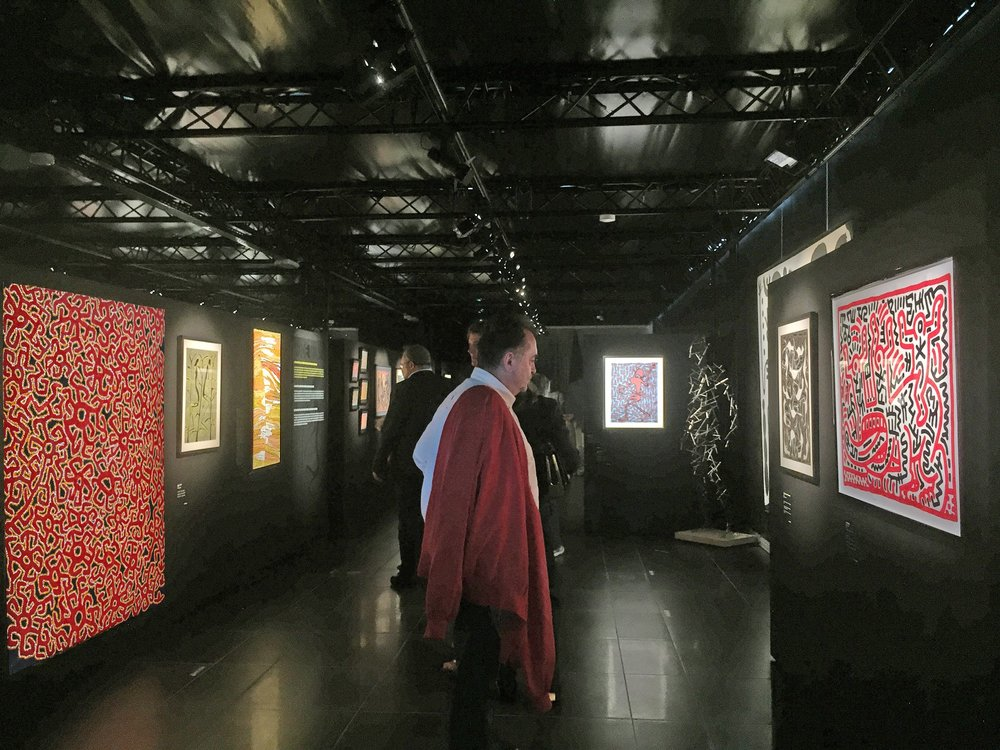 Vue de l'exposition retrospective Mode Muntu à la Cité Miroir à Liège. Dialogue entre une œuvre de l'artiste Aborigène Roy Underwood à gauche et une œuvre de l'artiste américain Keith Haring à droite.