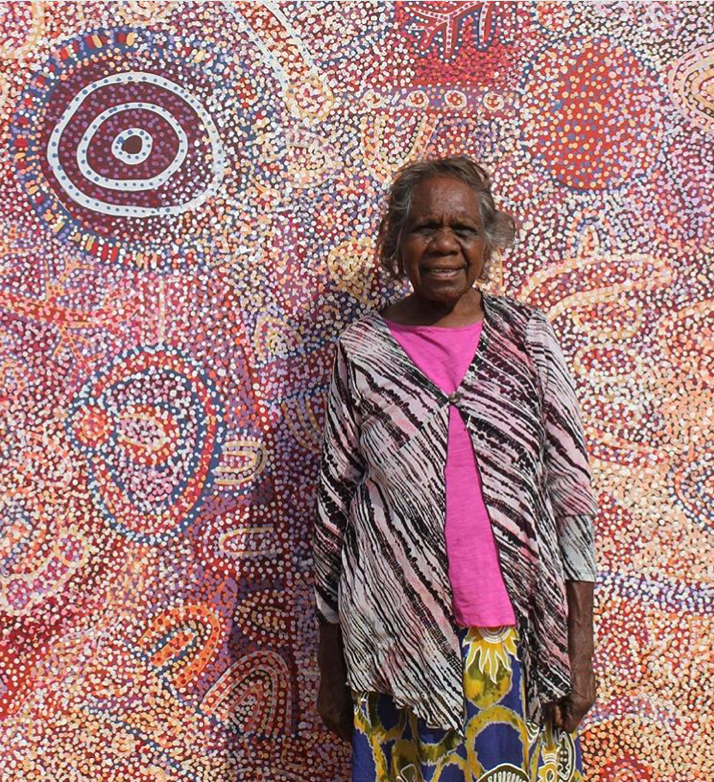 Portrait de l'artiste Ngupulya Pumani devant une de ses œuvres. © Photo : Mimili Maku Arts with the courtesy of the artist.