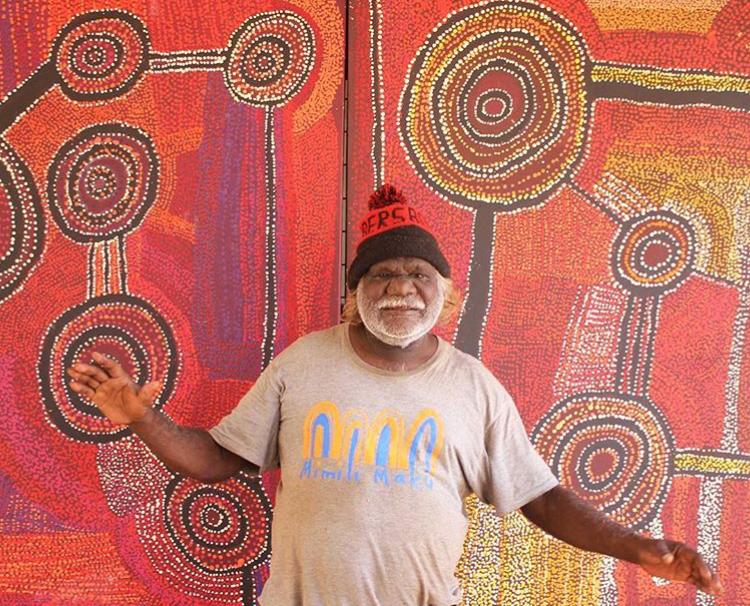 Portrait de l'artiste Willy Mutjanji Martin devant une de ses œuvres. © Photo : Mimili Maku Arts with the courtesy of the artist.