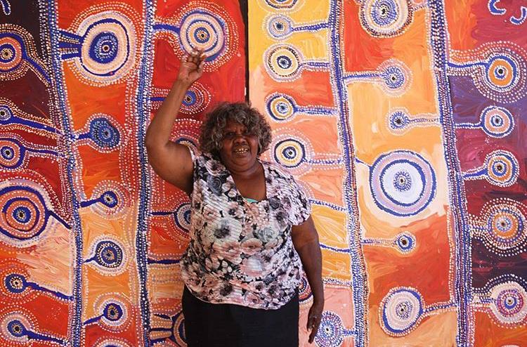 Portrait de l'artiste Tuppy Goodwin devant une de ses œuvres. © Photo : Mimili Maku Arts with the courtesy of the artist.