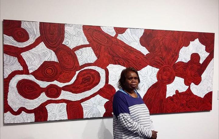 Portrait de l'artiste Betty Pumani devant une de ses œuvres. © Photo : Mimili Maku Arts with the courtesy of the artist.