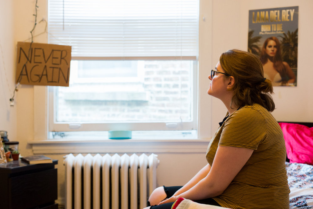 "Haggerty sits in her bedroom across from her 'NEVER AGAIN' sign. The sign symbolizes the era before Roe v. Wade when women resorted to coathanger abortions to end unwanted pregnancies. Haggerty made the sign for the ""March for Lies,"" a counter protest to the Illinois March for Life in Chicago."
