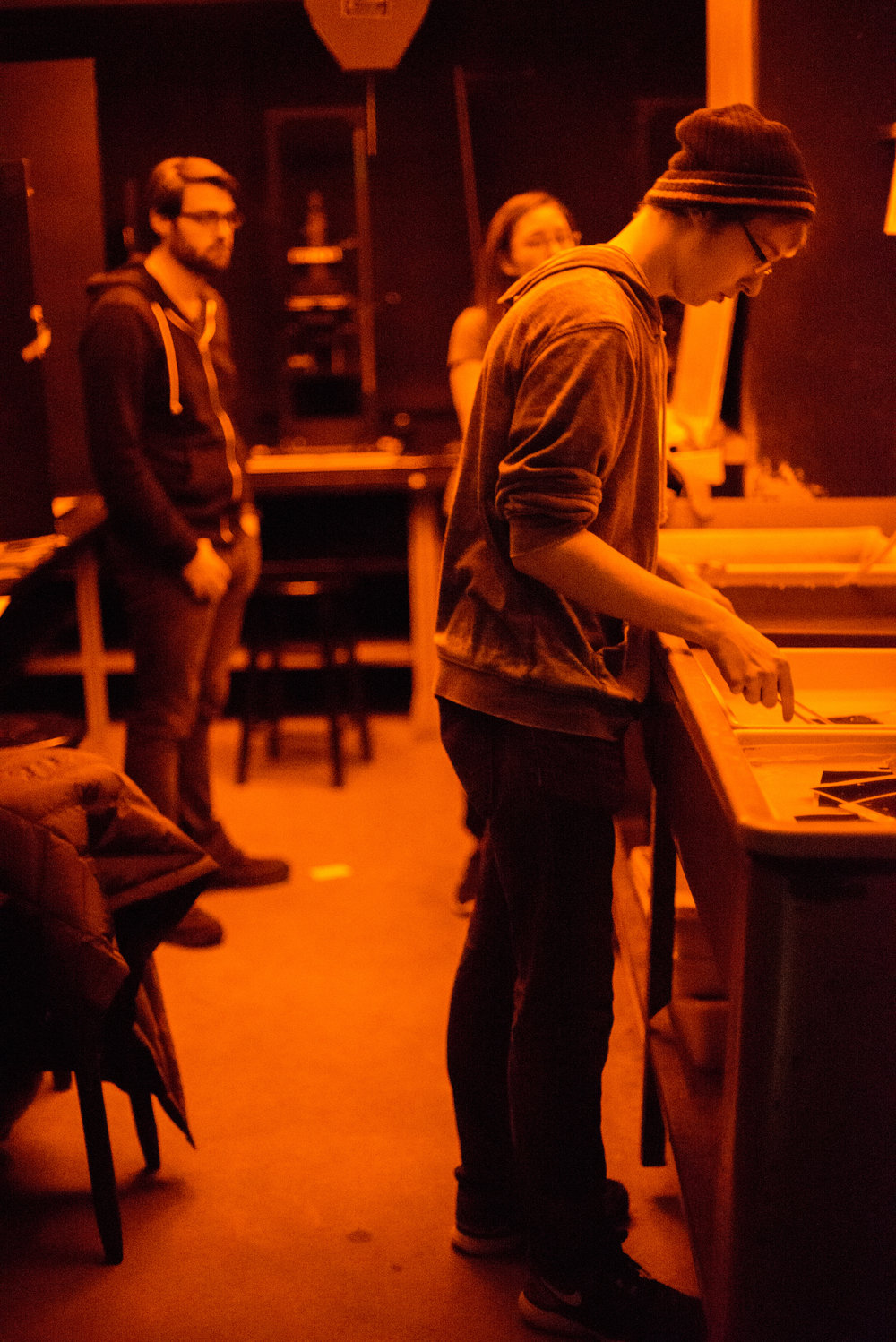 "Freshman Spencer Cox places his photosensitive paper in the fixer chemical for five minutes. Cox has extensive experience with digital photography, but his first time shooting film was this quarter for Intro to Photography. ""There's definitely a learning curve,"" Cox said. ""I think I've probably wasted 20 or 30 sheets of paper over the past few days. At this point, I am wasting less paper for every successful print, so it's getting better."""