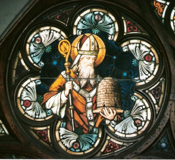 "Legend has it that a swam of bees landed on baby Ambrose's face and deposited a drop of honey. His father took it as a sing that the boy would grow up to speak eloquently with a ""honeyed"" tongue. For this reason Ambrose is often depicted with bees or a skep. This panel is part of the rose window at the Church of the Gesu, Milwaukee, WI"