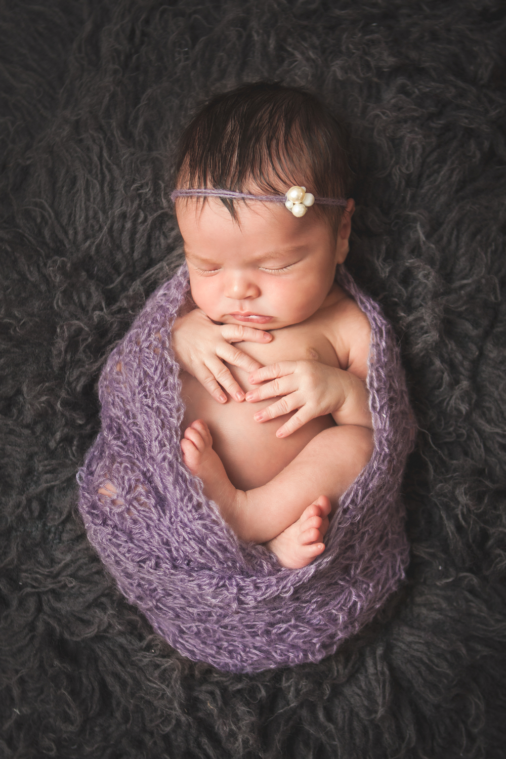Newborn baby girl wrapped in purple knit with pearl headband tieback on grey rug, Westchester County, NY Newborn Photographer Amanda Noelle Photography.