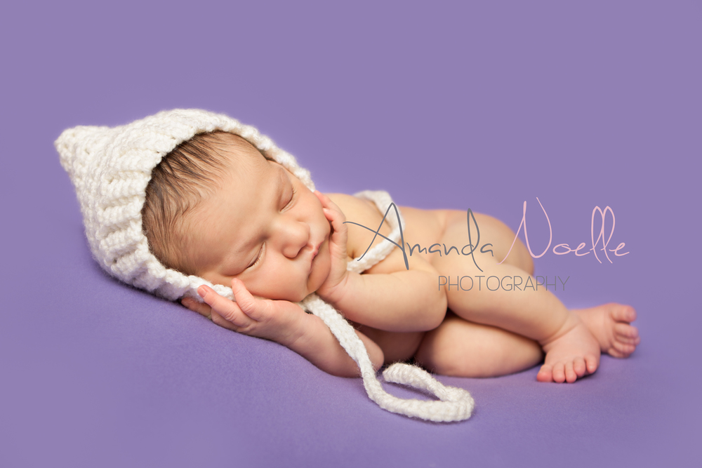 Newborn baby girl, purple background fabric, white pixie bonnet, sleeping pose, by Westchester, New York Newborn Photographer, Amanda Noelle Photography
