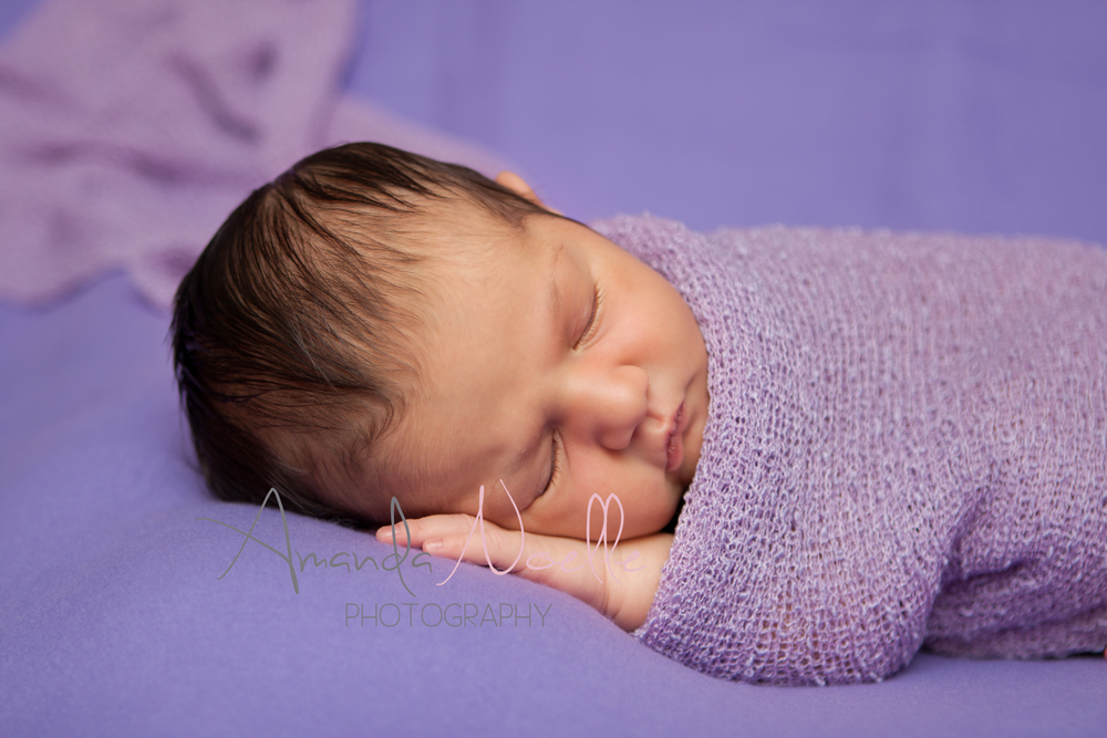 Newborn baby girl, purple background fabric, purple lilac stretch wrap draped, sleeping pose on beanbag, by Westchester, New York Newborn Photographer, Amanda Noelle Photography