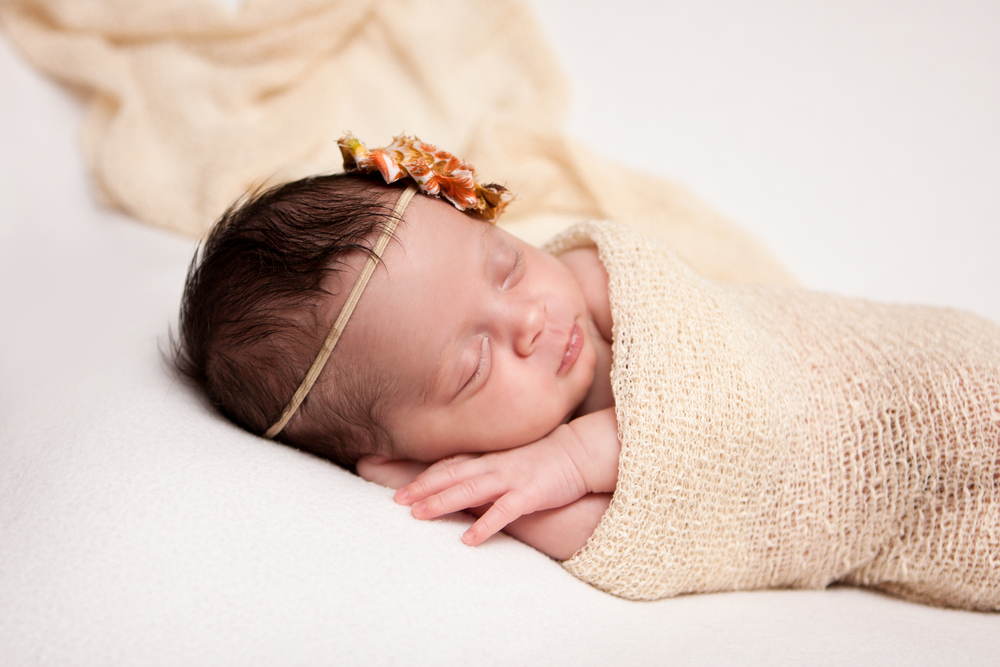 Newborn baby girl, shabby chic headband orange brown creme, creme white backdrop fabric blanket, creme tan stretch wrap, sleeping baby pose on beanbag, Westchester County, New Rochelle, White Plains, Pelham, New York Newborn Photographer, Amanda Noelle Photography