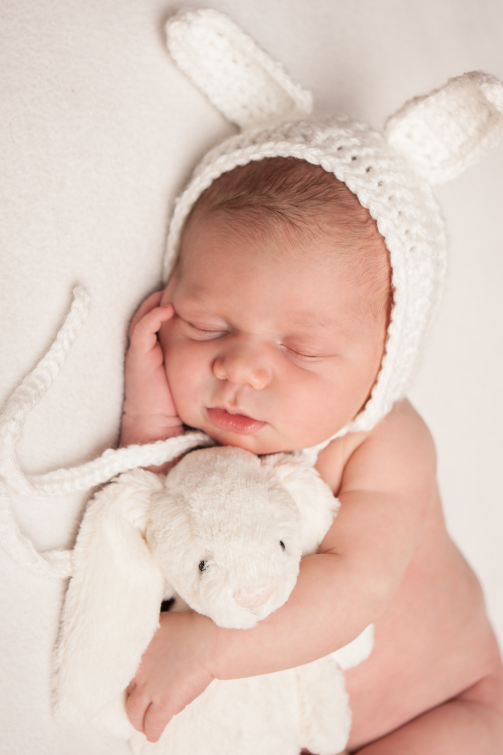 Newborn baby girl in crochet bunny bonnet, holding white bunny jellycat stuffed animal, bean bag pose, on white fabric backdrop, Westchester County, New York Newborn Photographer, Amanda Noelle Photography.