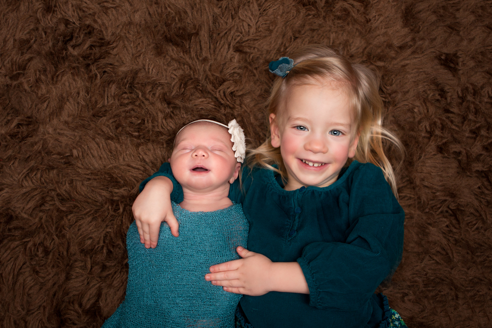 Newborn baby girl with big sister, siblings, sisters, on brown flokati rug dressed in teal turquoise with headbands  , Westchester County, New York Newborn Photographer, Amanda Noelle Photography.