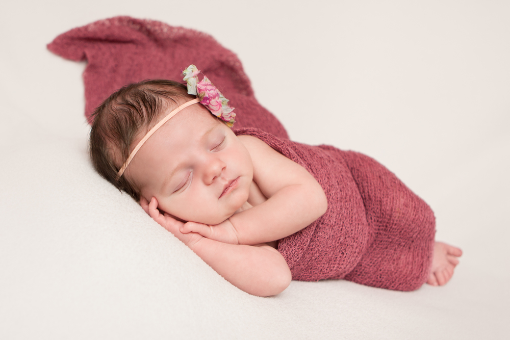 Newborn baby girl with pink mint creme shabby chic flower headband, pink berry maroon stretch wrap, on white fabric blanket backdrop, beanbag pose, Westchester County, New York Newborn Photographer, Amanda Noelle Photography.
