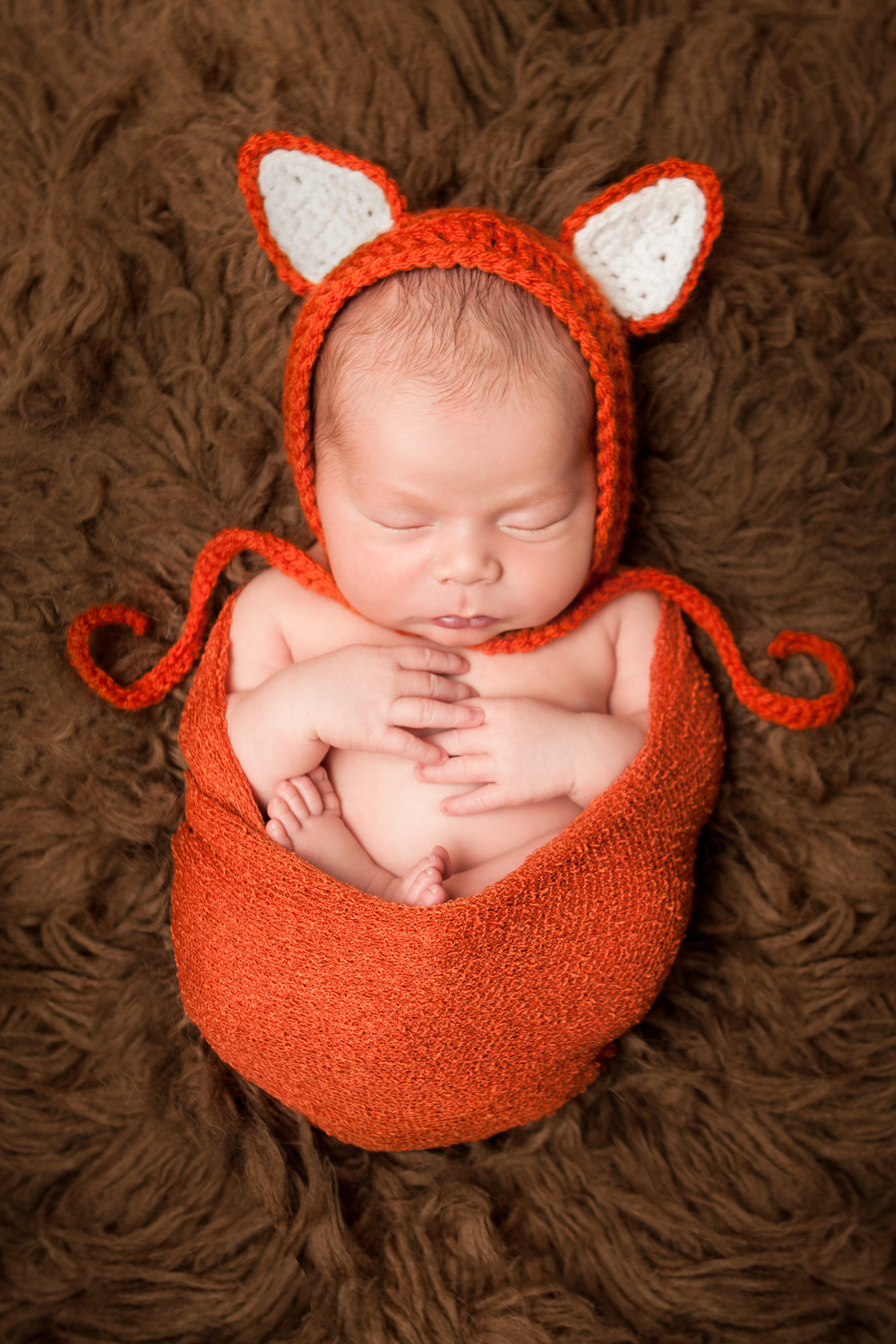 Newborn baby boy chubby orange crochet fox bonnet, orange stretch knit wrap on brown flokati rug, Westchester County, New York newborn photographer, Amanda Noelle Photography.