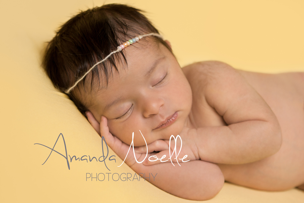 Newborn baby girl sleeping with rainbow bead tieback headband on yellow fabric backdrop, beanbag pose, Westchester, County New York Newborn Photographer, Amanda Noelle Photography.