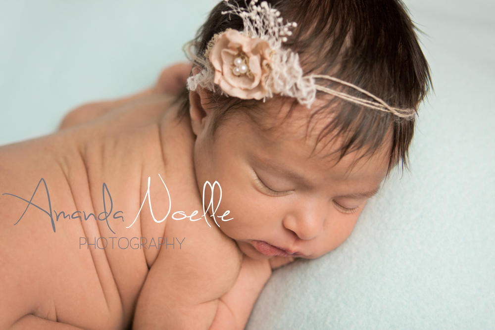 Newborn baby girl sleeping with shabby chic pink flower tieback   headband on teal mint aqua fabric backdrop, tushy up beanbag pose, Westchester, County New York Newborn Photographer, Amanda Noelle Photography.