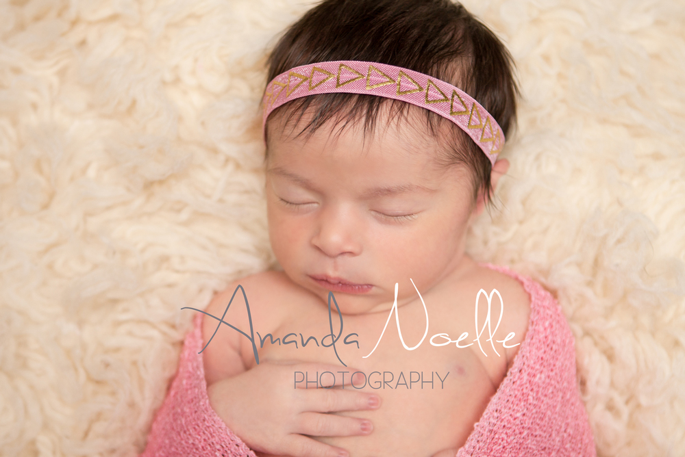 Newborn baby girl sleeping with pink and gold   headband wrapped in stretch knit pink wrap on cream creme flokati rug, Westchester, County New York Newborn Photographer, Amanda Noelle Photography.