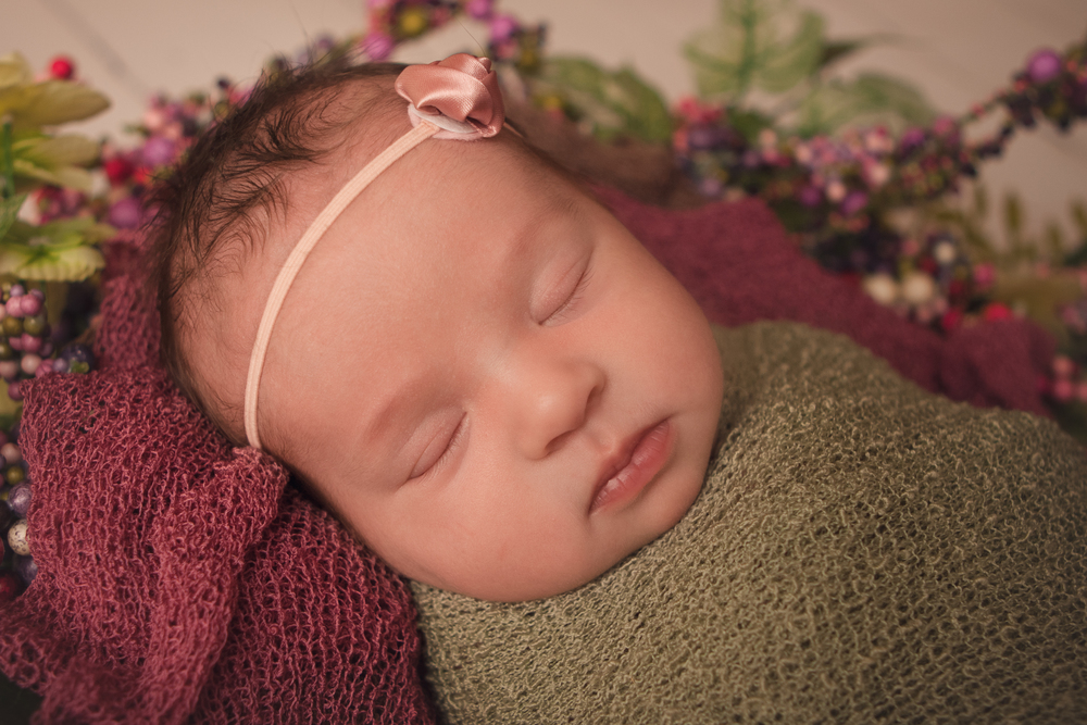 Newborn baby girl sleeping   spring photos, wrapped in green knit stretch wrap, spring wreath, white wood floor backdrop.