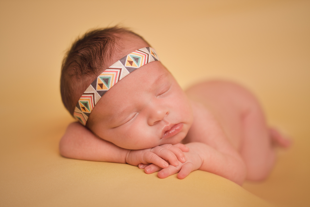 Newborn baby girl sleeping pose, bohemian headband, yellow blanket fabric backdrop, head chin on hands bean bag pose.