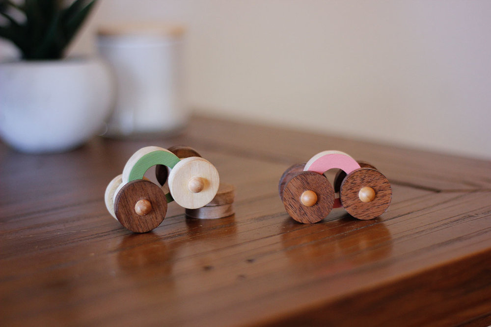 """option three - a more -out there- kind of ideas. a set of three mini wooden """"bubble"""" cars. cars are made of out hard maple wood and the wheels are cut out of a contrasting walnut wood. the bodies can be painted in any three colors of your choice. not sure about the type of packaging for these ones just yet."""