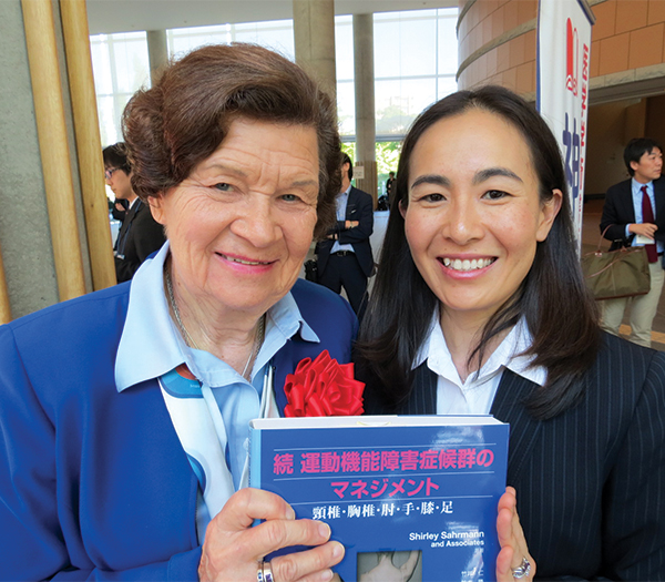Shirley Sahrmann (left) and Maiko Morotani pose with their work, the translation of Dr. Sahrmann's work into Japanese.