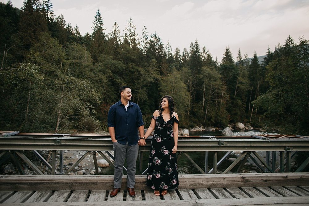 Copy of couple standing on bridge holding hands north beach trail
