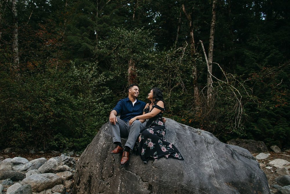Copy of couple sitting on rock laughing engagement photos