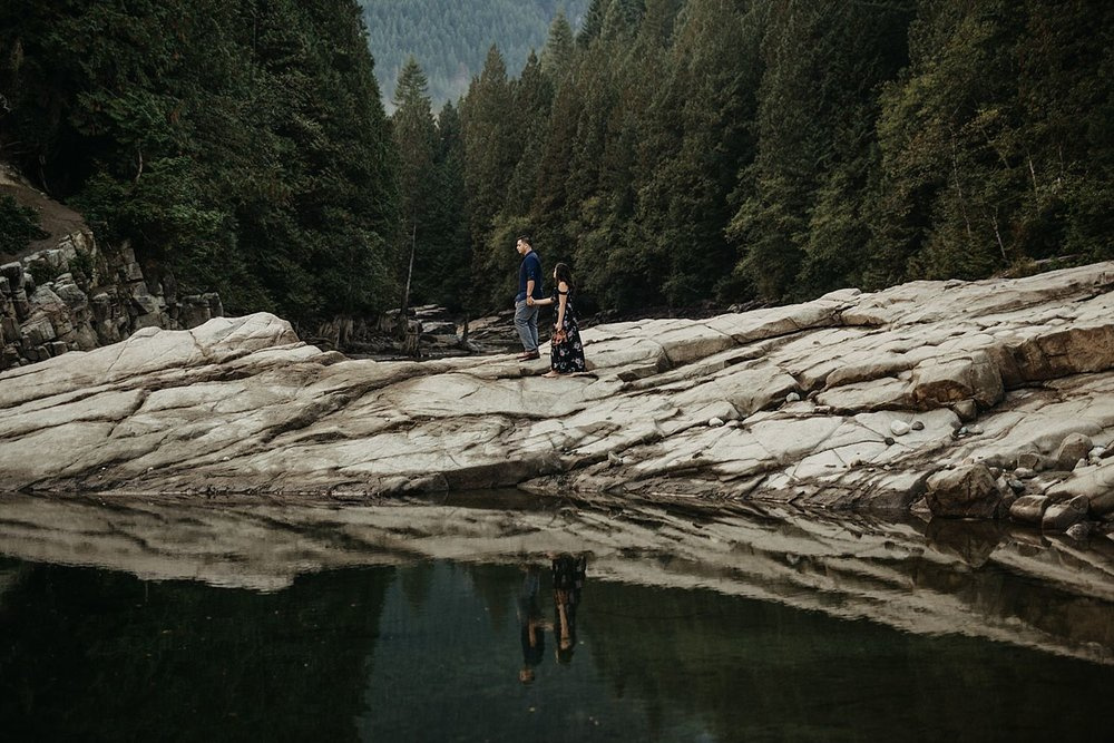 Copy of couple walking on rock reflection in water by trees