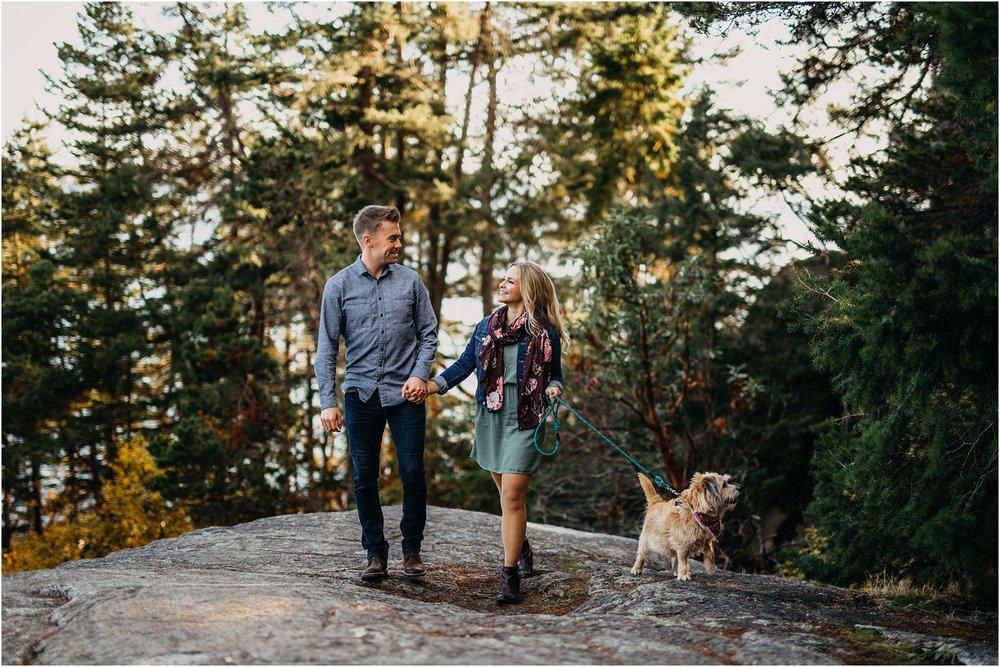 couple walking dog holding hands