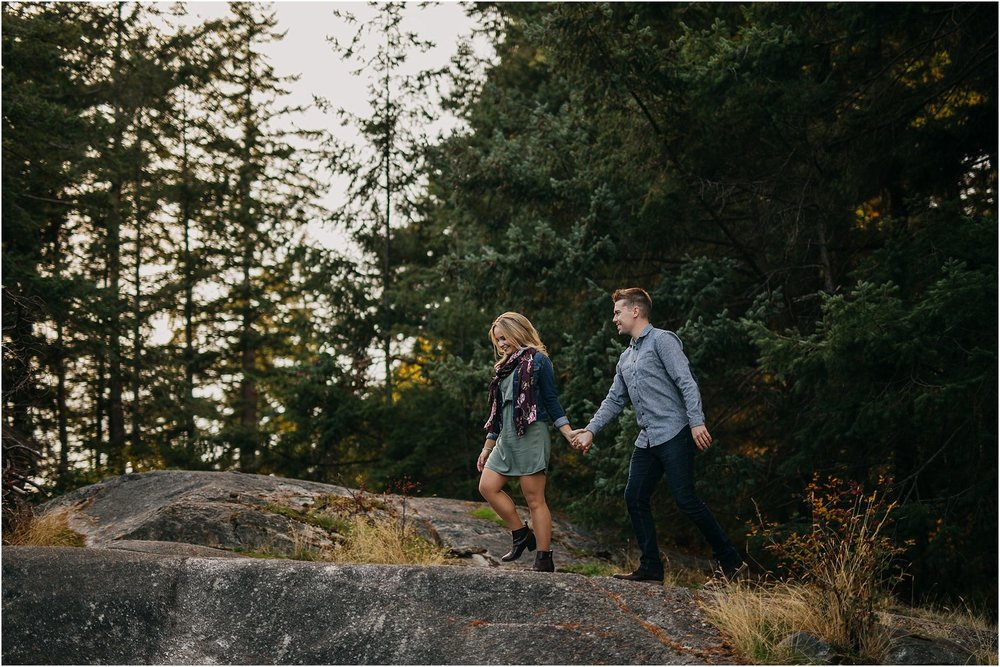 girl leading guy walking in forest
