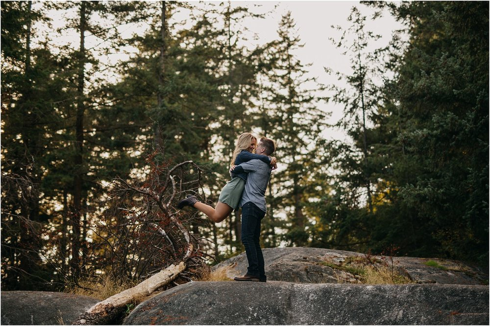 guy picking up girl kissing sunshine in forest