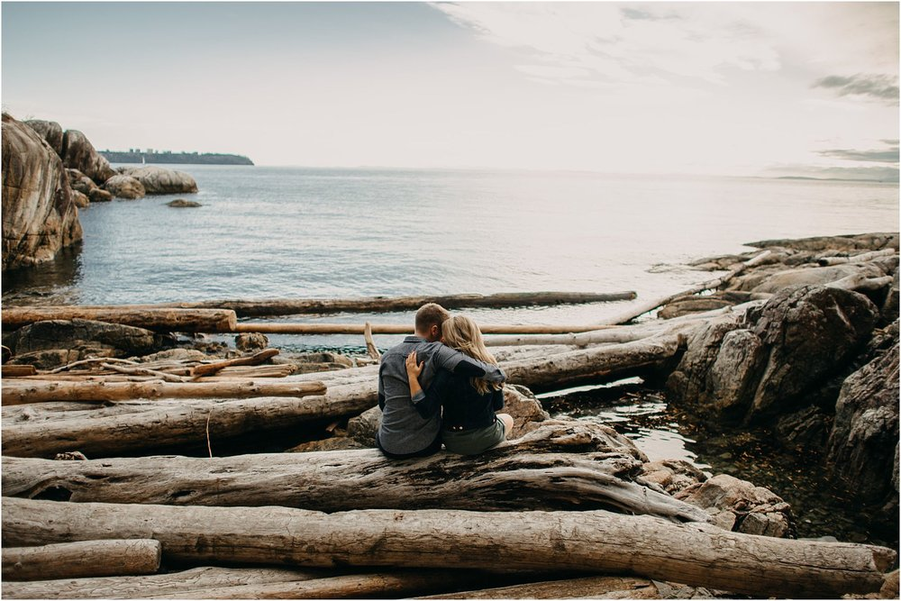 couple sitting on log lighthouse park ocean