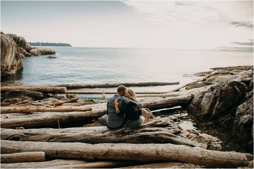 couple sitting on log lighthouse park ocean