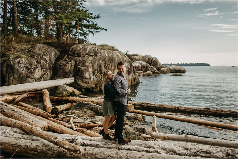 woman hugging man standing on logs ocean lighthouse park