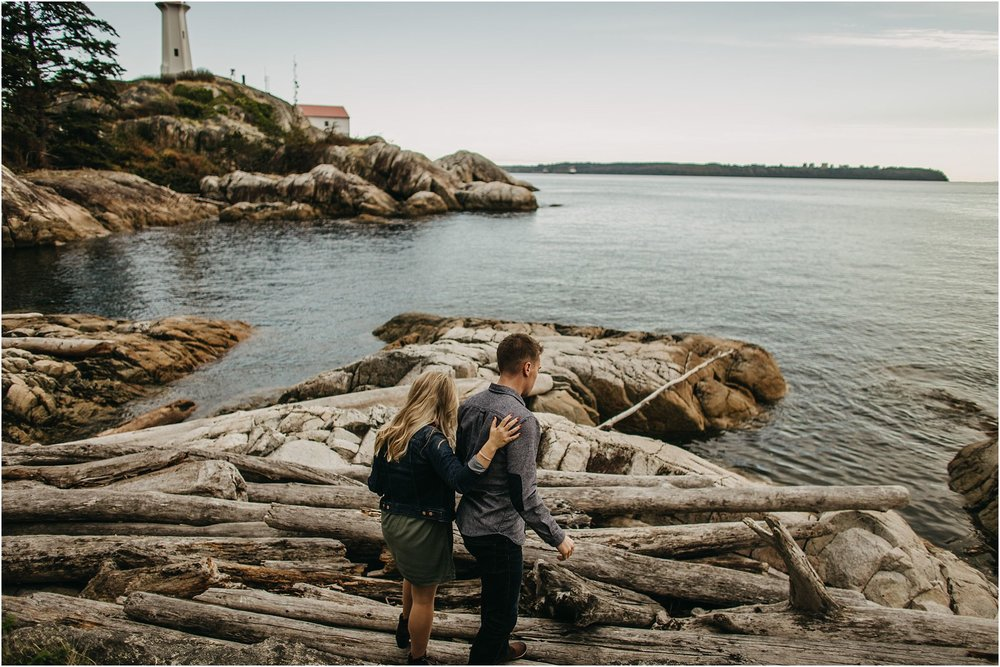 couple walking on logs at beach lighthouse park