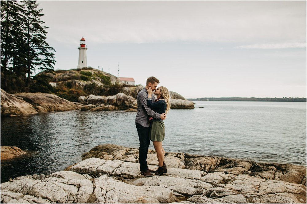 couple kissing on beach at lighthouse park