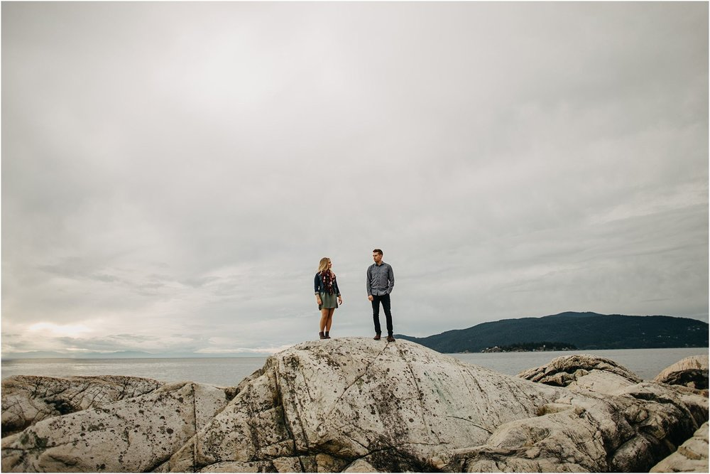 couple standing on top of rock by ocean at lighthouse park