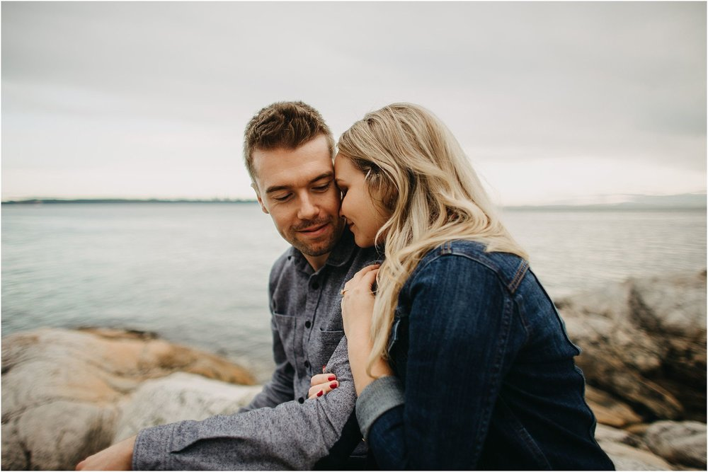 couple snuggling by ocean engagement session