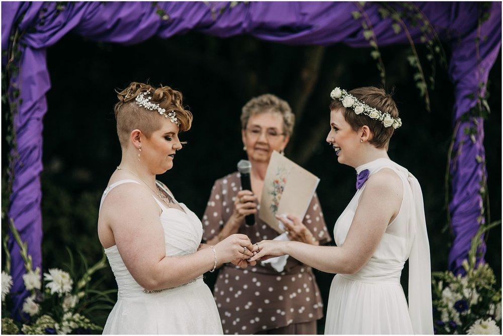 same sex couple exchanging rings wedding