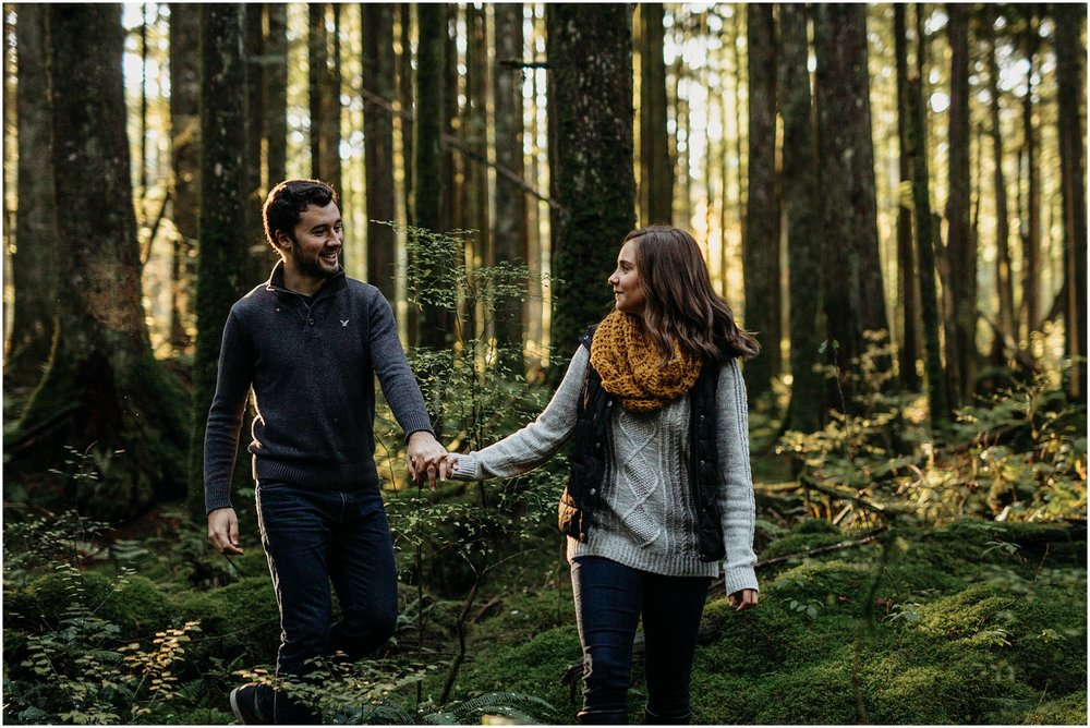 girl leading guy out of forest engagement session