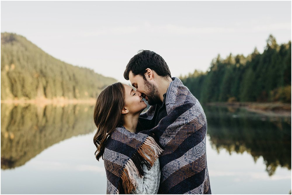 couple wrapped in blanket lake reflection rolley lake engagement