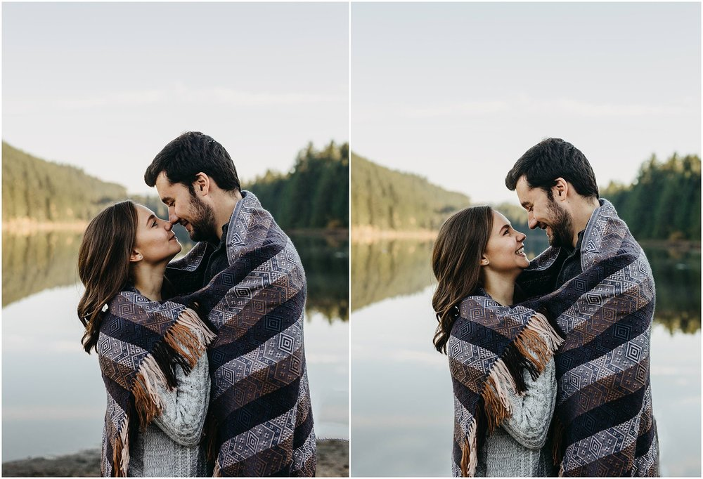 couple wrapped up in blanket fall engagement session lake reflection