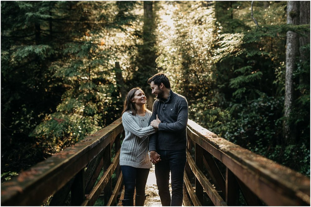 couple walking on bridge sun shining through trees rolley lake engagement