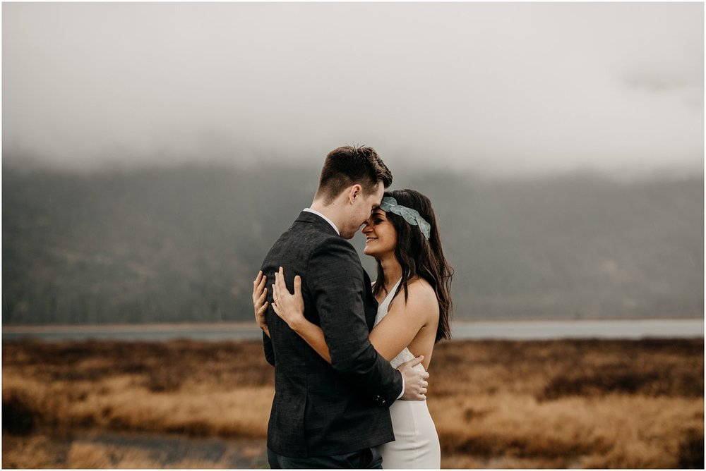 couple hug foggy pitt lake engagement photos