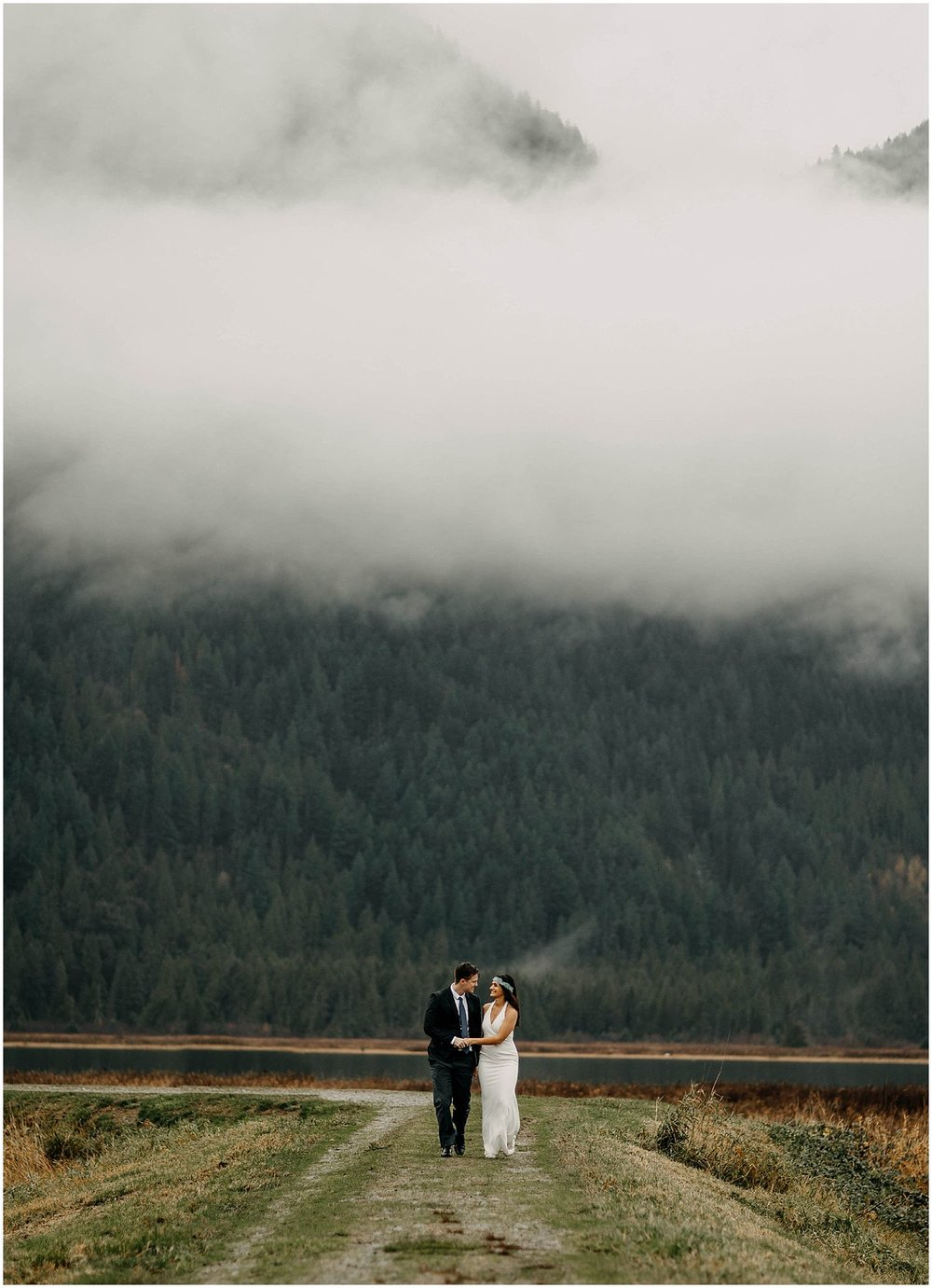 couple walking along pitt lake marsh cloud fog mountains engagement