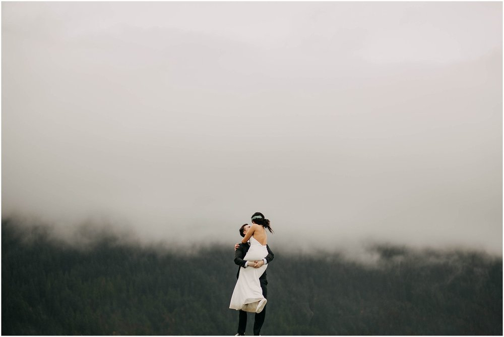 couple spinning around foggy cloudy minimal pitt lake engagement