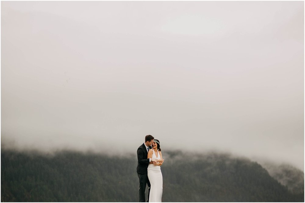 bride and groom in front of foggy mountains pitt lake