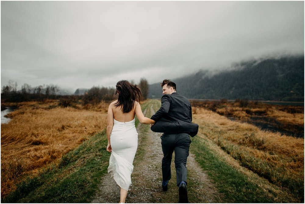 couple holding hands running away on pitt lake marsh