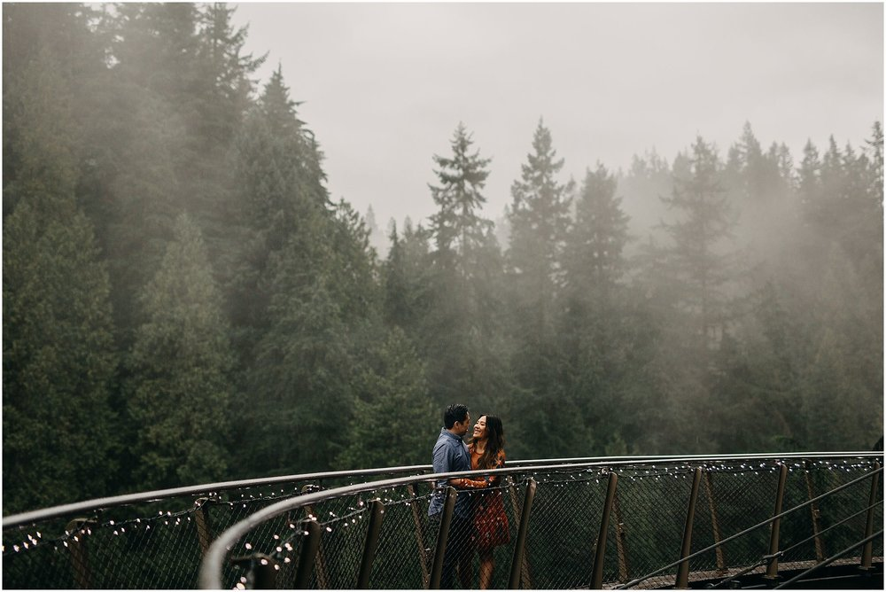 engaged couple on cliffwalk capilano suspension bridge fog rain trees