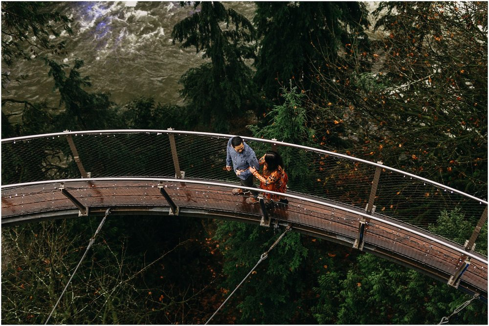 engaged couple holding hands walking on cliffwalk capilano suspension bridge