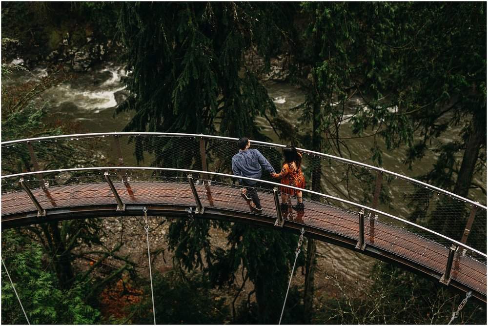 engaged couple holding hands walking along cliffwalk capilano suspension bridge
