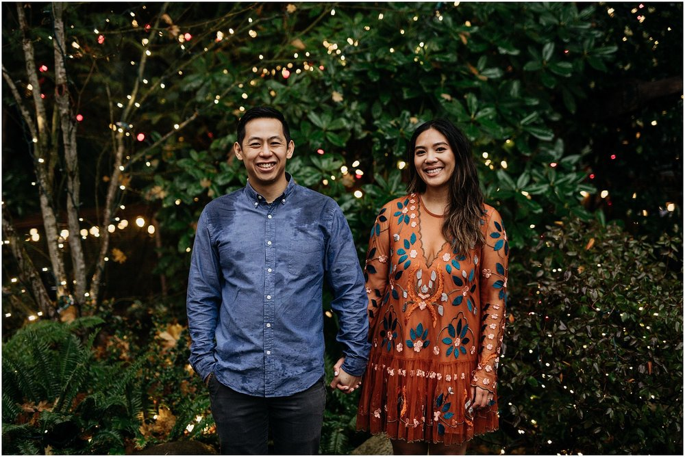 couple engagement standing in capilano suspension bridge canyon lights